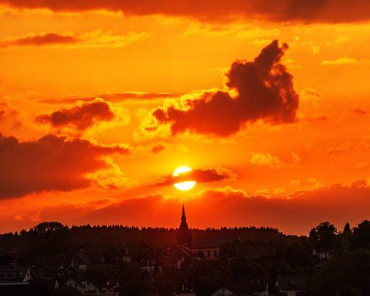 """Diesen spektakulären Sonnenuntergang konnte man an Christi Himmelfahrt, 10. Mai 2018, in Drabenderhöhe beobachten. Um 20:46 Uhr stand die Sonne, von der Kronstädter Gasse aus gesehen, genau über der Kirchturmspitze. Foto: <a href=""""http://www.melzer.de"""">Günther Melzer</a>"""