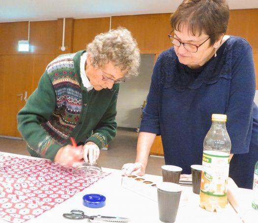 Kathi Fink (rechts) schaut Ingrid Bosch beim Zuschneiden der Deckchen zu