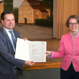 Mit großer Freude nimmt Bürgermeister Ulrich Stücker den Förderbescheid aus den Händen von NRW-Bauministerin Ina Scharrenbach entgegen.